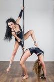 Muchachas flexibles que hacen trucos acrobáticos difíciles con un polo Fotos de archivo