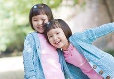 Muchachas gemelas asiáticas sonrientes fotografía de archivo libre de regalías