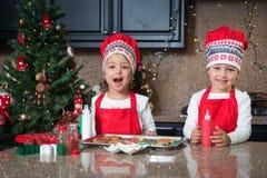 Muchachas gemelas felices en el rojo que hace las galletas de la Navidad Fotografía de archivo
