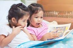 Muchachas gemelas preciosas del niño de la hermana dos que se divierten para leer una historieta Fotografía de archivo