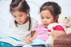 Muchachas gemelas preciosas del niño de la hermana dos que se divierten para leer una historieta Imágenes de archivo libres de regalías