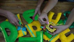 Muchachas hechas a mano que cosen letras del fieltro metrajes