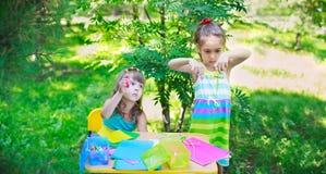 Muchachas, hermanas, niños, amigos que cortan al aire libre de papel multicolor imagenes de archivo