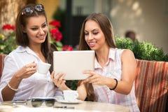 Muchachas hermosas con la tableta en el café Fotografía de archivo libre de regalías