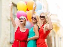 Muchachas hermosas con los globos coloridos en la ciudad imagen de archivo