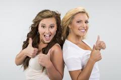 2 muchachas hermosas con los pulgares para arriba Fotografía de archivo