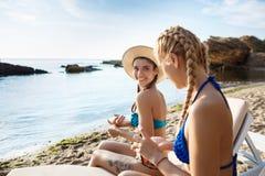 Muchachas hermosas en la sonrisa del traje de baño, aplicando la crema del bronceado en la playa Imagenes de archivo