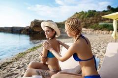 Muchachas hermosas en la sonrisa del traje de baño, aplicando la crema del bronceado en la playa Imagen de archivo