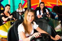 Muchachas hermosas en un coche de parachoques eléctrico adentro Fotografía de archivo libre de regalías