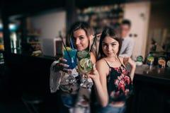 Muchachas hermosas jovenes con los cócteles cerca de la barra fotografía de archivo