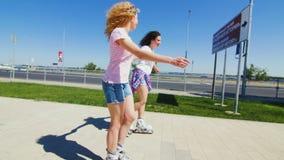 Muchachas hermosas jovenes Rollerblading en un parque almacen de video