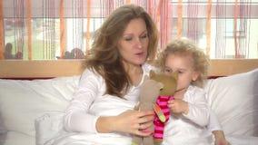 Muchachas hermosas mamá de la familia e hija del niño que juega con los gatos del juguete en dormitorio almacen de metraje de vídeo