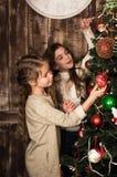 Muchachas hermosas que adornan el árbol de navidad Imagen de archivo