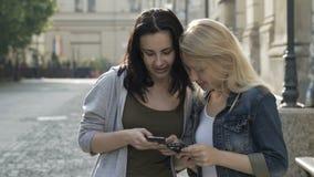 Muchachas hermosas que cuelgan hacia fuera tener una conversación y usar smartphones mientras que camina almacen de metraje de vídeo