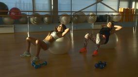 Muchachas hermosas que entrenan en fitball en el gimnasio almacen de video