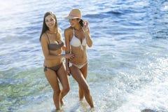 Muchachas hermosas que gozan de verano y de la agua de mar Imagen de archivo