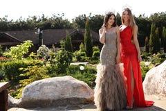 Muchachas hermosas que llevan los vestidos elegantes y la corona lujosa Imagen de archivo libre de regalías