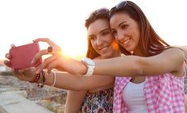 Muchachas hermosas que toman un selfie en el tejado en la puesta del sol Fotografía de archivo libre de regalías