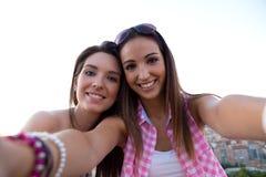Muchachas hermosas que toman un selfie en el tejado en la puesta del sol Foto de archivo libre de regalías