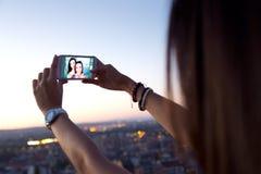 Muchachas hermosas que toman un selfie en el tejado en la puesta del sol Imagenes de archivo