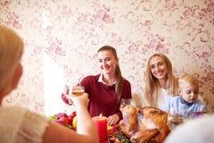 Muchachas hermosas y bebé que se sientan en la tabla festiva en un fondo casero Familia que sonríe en la cena de la Navidad foto de archivo libre de regalías
