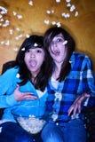 Muchachas hispánicas asustadas con palomitas Foto de archivo libre de regalías