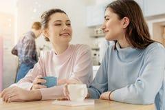 Muchachas interesadas sonrientes en café Imágenes de archivo libres de regalías