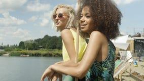Muchachas jovenes hermosas de la raza mixta que hablan cerca del lago y que disfrutan de vacaciones Fotos de archivo libres de regalías