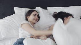 Muchachas lesbianas felices que caen en cama con las almohadas Est?n riendo, se est?n divirtiendo y est?n mirando uno a C?mara le almacen de metraje de vídeo