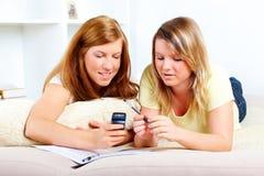 Muchachas lindas con el teléfono móvil y los papeles de la computadora portátil Fotografía de archivo libre de regalías