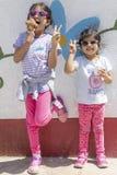 Muchachas lindas con las gafas de sol que comen un helado delicioso imagen de archivo