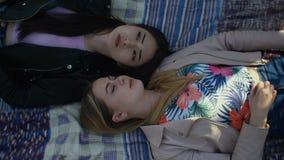 Muchachas lindas diversas que descansan sobre césped del parque en primavera metrajes
