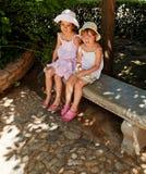 Muchachas lindas en banco Imagen de archivo libre de regalías