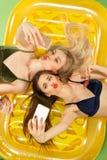 Muchachas lindas en los trajes de baño que presentan en el estudio Adolescentes caucásicos del retrato del verano en fondo rosado Foto de archivo libre de regalías