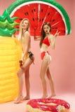 Muchachas lindas en los trajes de baño que presentan en el estudio Adolescentes caucásicos del retrato del verano en fondo rosado Imagen de archivo