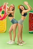 Muchachas lindas en los trajes de baño que presentan en el estudio Adolescentes caucásicos del retrato del verano en fondo verde Fotografía de archivo