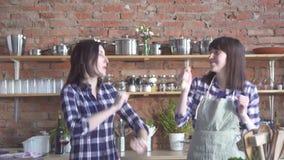 Muchachas lindas que bailan y que cantan en la cocina mientras que cocina almacen de metraje de vídeo