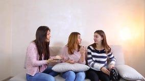 Muchachas lindas que miran y que estudian el reloj elegante elegante, sentándose en el sofá en dormitorio brillante almacen de metraje de vídeo