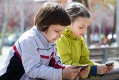 Muchachas lindas que presentan con los móviles Fotos de archivo libres de regalías