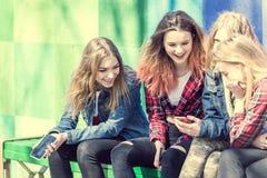 Muchachas lindas que se sientan en el banco en el parque y la risa Imágenes de archivo libres de regalías