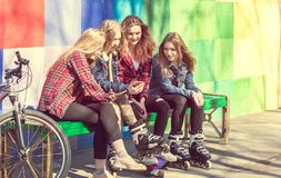 Muchachas lindas que se sientan en el banco en el parque y la risa Foto de archivo
