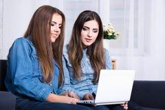 Muchachas lindas que usan el ordenador portátil en casa Fotos de archivo