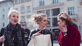 Muchachas modernas jovenes que se divierten en el centro de ciudad, compartiendo secretos y la risa Moda-expertos elegantes que v almacen de metraje de vídeo