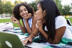 Muchachas multiétnicas jovenes sonrientes felices de los amigos que hacen la preparación usando el ordenador portátil al aire lib imagen de archivo libre de regalías