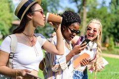 Muchachas multiétnicas que usan smartphone y bebiendo el café de la taza de papel en parque Fotos de archivo