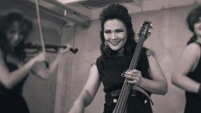 Muchachas muy frescas en el negro que toca el violín Músicos artísticos maravillosos almacen de video