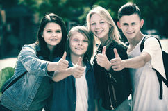 Muchachas positivas y muchachos que presentan con los pulgares para arriba Imagen de archivo libre de regalías