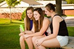 muchachas Pre-adolescentes que mandan un SMS mientras que cuelga hacia fuera en frente  Imagen de archivo