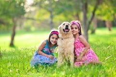 Muchachas que abrazan el perro perdiguero de oro en el parque fotografía de archivo libre de regalías