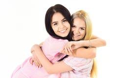 Muchachas que abrazan firmemente, aislado en el fondo blanco Hermanas o mejores amigos en pijamas Concepto de los mejores amigos  Fotografía de archivo